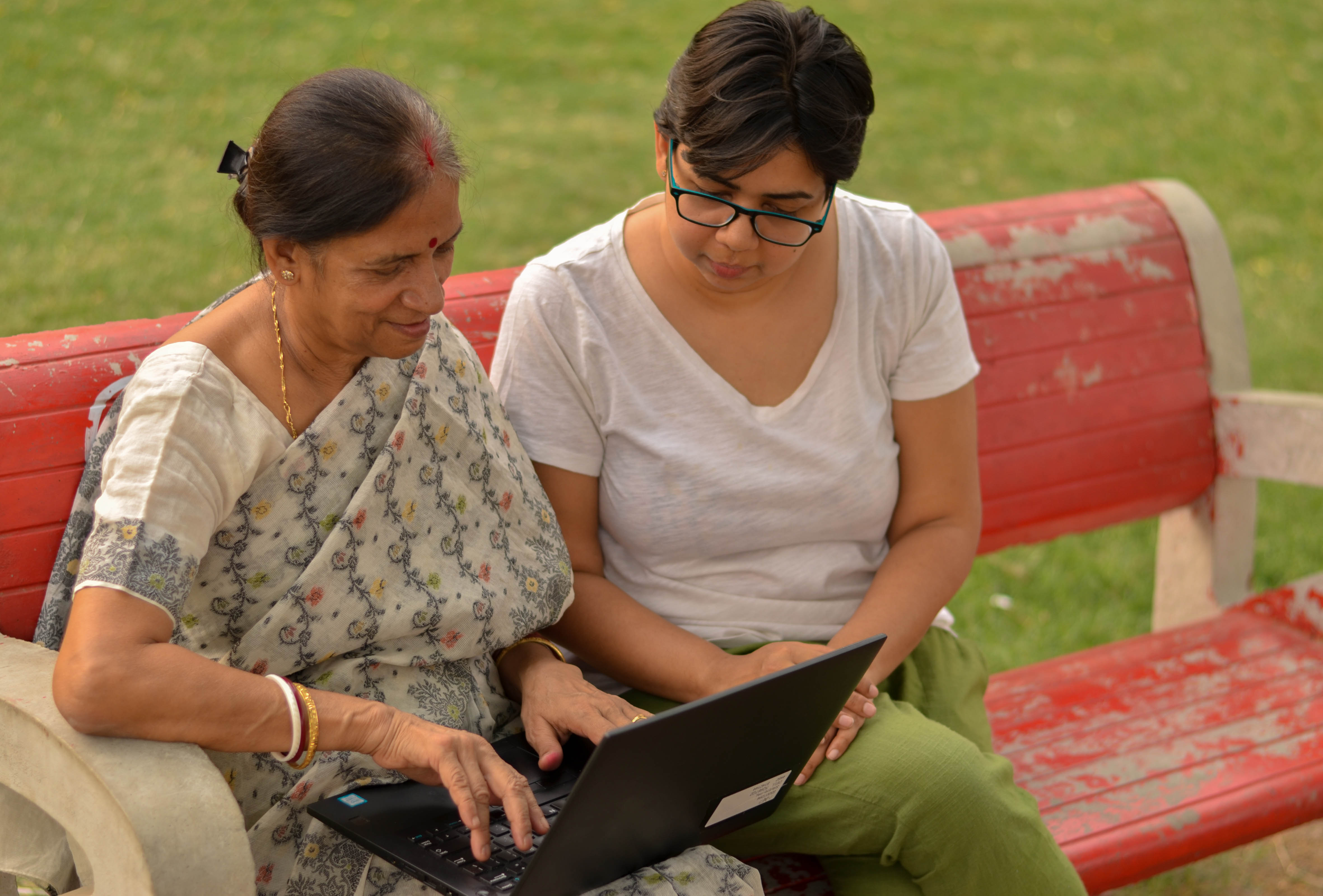 Young Indian girl helping an old Indian woman on a laptop