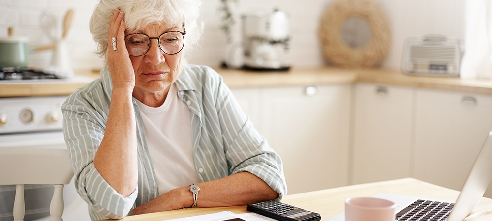 Sad Elderly woman at kitchen table
